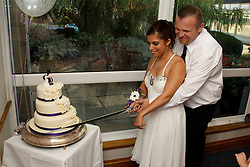 Bride who has cerebral palsy, with groom at wedding ceremony cutting cake with a sword.