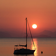 Silhouette of a boat and mountains at sunrise, Turunc, Turkey