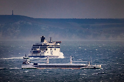 © Licensed to London News Pictures. 18/12/2020. Dover, UK. <br /> A P&O ferry is passed by a cargo ship as it heads for France (top) from Port of Dover. Retailers are suggesting that delays at some ports are causing shortages of goods in the shops this Christmas. Photo credit: Peter Macdiarmid/LNP