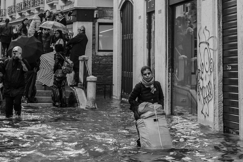 Venice, Italy. 29 October, 2018. A woman carries her goods in a flooded street during the high tide in Strada Nova on October 29, 2018, in Venice, Italy. This is a selection of pictures of different areas of Venice that the press has not covered, were resident live and every year they have to struggle with the high tide. Due to the exceptional level of the 'acqua alta' or 'High Tide' that reached 156 cm today, Venetian schools and hospitals were closed by the authorities, and citizens were advised against leaving their homes. This level of High Tide has been reached in 1979. © Simone Padovani / Awakening / Alamy Live News