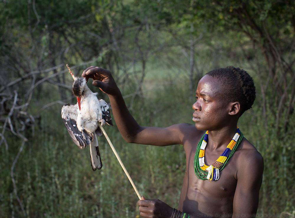 Young Hadza men hunting birds. At the Hadza camp of Dedauko.