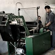 """Trabajadores """"Zabbaleen"""" en una de las máquinas que produce bolsas de basura con plástico reciclado en la planta de reciclaje de Katameya, que dirige la ONG A.P.E. en las afueras del Cairo. En medio del barrio de Manshiet Nasr a las afueras de El Cairo esta situado el asentamiento de Mokattam conocido como la """"Ciudad de la Basura"""" , está habitado por los Zabbaleen ,una comunidad de unos 45.000 cristianos coptos que viven desde hace varias décadas de reciclar los desperdicios que genera la capital egipcia: plástico, aluminio, papel y desechos órganicos que transforman en compost . La mayoría forman parte de la Asociación para la Protección del Ambiente (APE) una ONG que actúa en el área, cuyos objetivos son proteger el medio ambiente y aumentar el sustento de las recuperadores de basura de El Cairo. Según la ONU, el trabajo que se realiza en Mokattam como uno de los diez mejores ejemplos del mundo en el mejoramiento medioambiental. El Cairo , Egipto, Junio 2011. ( Foto : Jordi Camí )"""