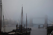 Thick fog over London at Tower Bridge making a peaceful yet eerie atmosphere as structures appear and disappear over the River Thames. Here at Hermitage Wharf, barges are moored which gives an impression we are looking at a scene from a previous century.