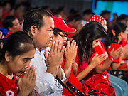 27 JULY 2013 - BANGKOK, THAILAND:  Thai Red Shirts pray at the beginning of their birthday party for Thaksin Shinawatra. The Red Shirts celebrated former Prime Minister Thaksin Shinawatra's 64th birthday with a party at Phibun Prachasan School in Bangkok. They had a Buddhist Merit Making Ceremony, dinner, cake and entertainment. Most of the Red Shirt political elite traveled to Hong Kong for a party with Thaksin. Thaksin, the former Prime Minister, was deposed by a coup in 2006 and subsequently convicted of corruption related crimes. He went into exile rather than go to jail but remains very popular in rural parts of Thailand. His sister, Yingluck Shinawatra is the current Prime Minister and was elected based on her brother's recommendation.    PHOTO BY JACK KURTZ