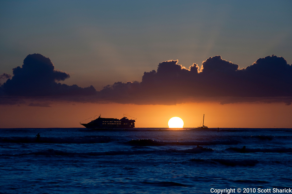 A boat and sailboat move across the horizon as the sun hits the ocean water.