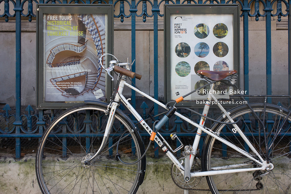 A poster of circles and spirals and Impressionist art with a locked bicycle on railings outside Somerset House, Aldwych, central London.