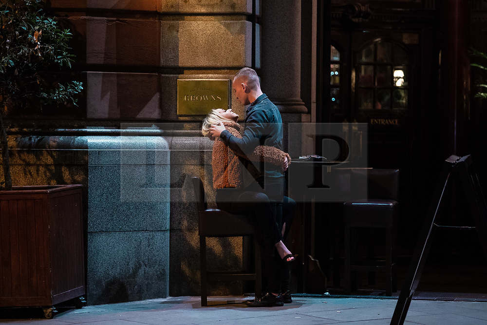 © Licensed to London News Pictures . 27/10/2018. Manchester, UK. A couple embrace outside a club on King Street , in Manchester City Centre . Revellers on a night out , many in fancy dress , on the weekend before Halloween . Photo credit: Joel Goodman/LNP