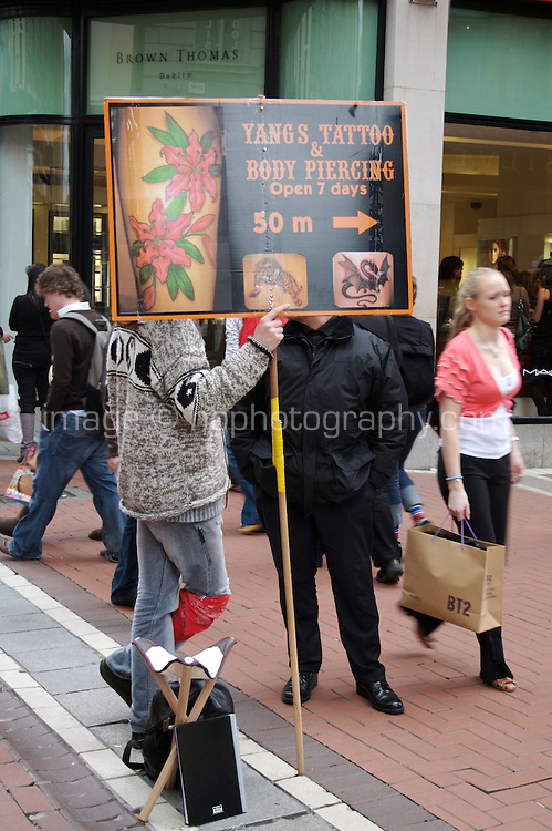 Man holding advertisement for tattoo and body piercing shop on Grafton Street in Dublin Ireland