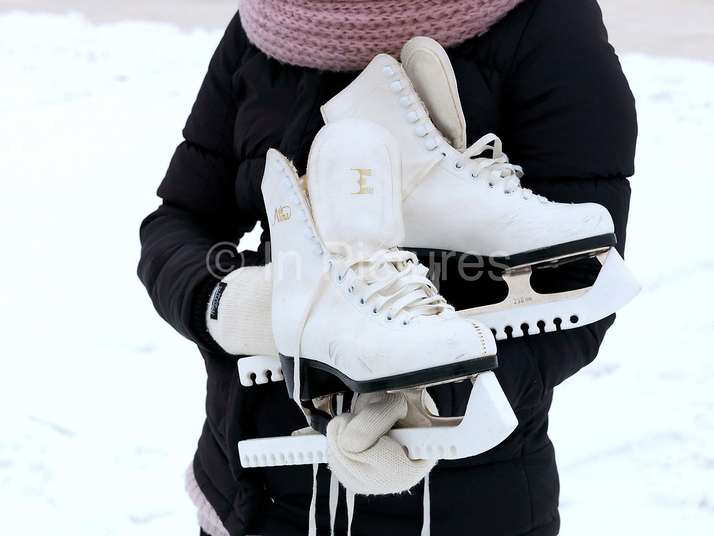 A woman stands with her ice-skating boots at Jyvasjarvi lake, Jyvaskyla, Central Finland. Jyvaskyla is the capital of Central Finland and the largest city in the Finnish Lakeland, an area of more than 188,000 lakes. During the Winter, the city is transformed and the lakes which surround it become a temporary urban park with a specially constructed ice skating.