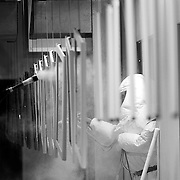 Powder coating operation, spraying line of metal parts in spray room.