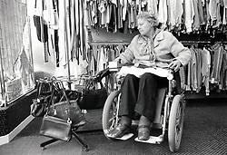 Elderly woman in wheelchair in charity shop, Nottingham UK 1989