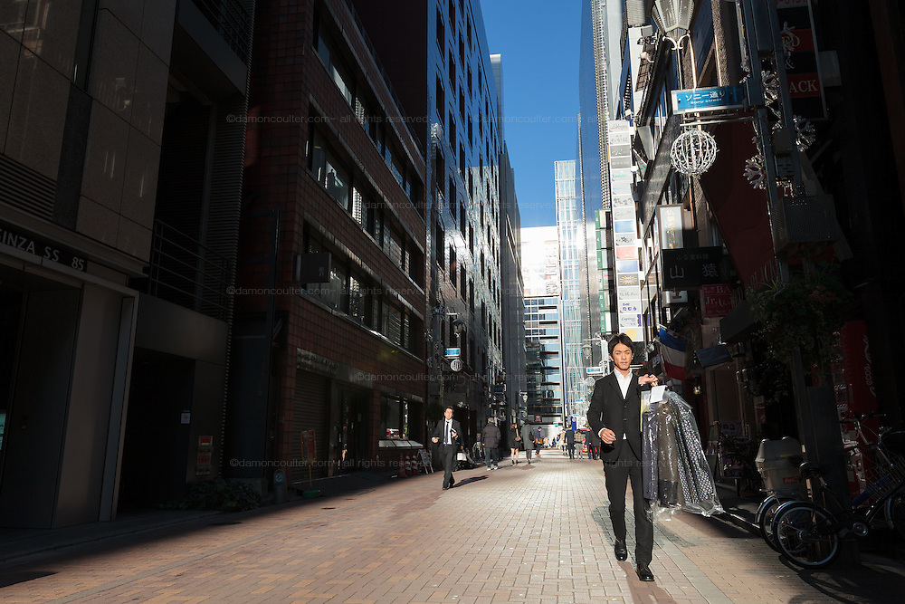A fashionable japanese office worker or salaryman carries clothes in a sunlit street in Ginza, Tokyo, Japan. Friday December 18th 2015