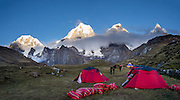 Sunrise hits the Cordillera Huayhuash above Carhuacocha campground (13,600 feet) in the Andes Mountains, Peru, South America. Peaks from left to right are: Siula Grande, Yerupaja Grande (6635 m or 21,770 ft, highest point in the Amazon watershed), Yerupaja Chico, and Mount Jirishanca (Icy Beak of the Hummingbird). Day 3 of 9 days trekking around the Cordillera Huayhuash. This panorama was stitched from 2 overlapping photos.