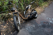 The wreckage of a burned-out scooter leans abandoned against fencing in an alleyway in Beckenham, on 14th June 2020, in London, England.