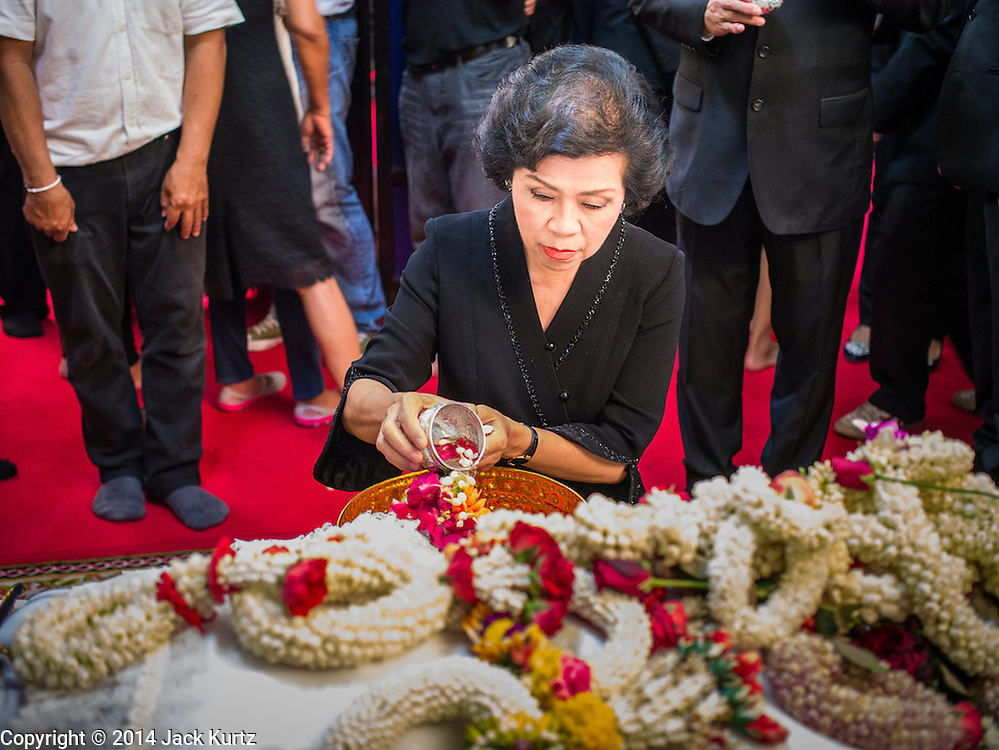 12 OCTOBER 2104 - BANG BUA THONG, NONTHABURI, THAILAND: A woman pours scented water over the hand of Apiwan Wiriyachai on the first day of Apiwan's funeral rites at Wat Bang Phai in Bang Bua Thong, a Bangkok suburb, Sunday. Apiwan was a prominent Red Shirt leader, member of the Pheu Thai Party of former Prime Minister Yingluck Shinawatra, and a member of the Thai parliament. The military government that deposed the elected government in May, 2014, charged Apiwan with Lese Majeste for allegedly insulting the Thai Monarchy. Rather than face the charges, Apiwan fled Thailand to the Philippines. He died of a lung infection in the Philippines on Oct. 6. The military government gave his family permission to bring him back to Thailand for the funeral. He will be cremated later in October. The first day of the funeral rites Sunday drew tens of thousands of Red Shirts and their supporters, in the first Red Shirt gathering since the coup.    PHOTO BY JACK KURTZ