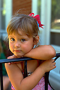 Child age 3 leaning on railing fence with curious look on face.  WesternSprings  Illinois USA