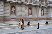 People interact with statues of reknowned men outside the Royal Academy of Arts on 3rd July 2021 in London, United Kingdom. The opposite figures gives a juxtaposition of the vastly different eras.