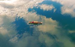 July 19, 2017 - Zixing, China - Clouds are reflected as a boat floats on the Xiaodong Jiang river in Zixing, central China's Hunan Province.  (Credit Image: © Cao Zhengping/Xinhua via ZUMA Wire)