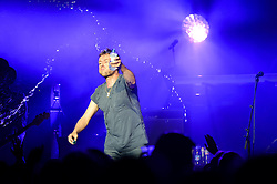 © Licensed to London News Pictures. 15/11/2014. London, UK.   Damon Albarn sprays the audience with water as he performs live at Royal Albert Hall with backing band The Heavy Seas.  Albarn is touring to promote his first solo record, Everyday Robots.   Photo credit : Richard Isaac/LNP