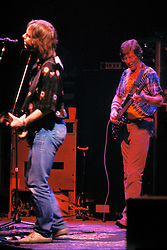 Bob Weir and Phil Lesh performing with the Grateful Dead in Concert at the Brendan Bryne Arena on April 1st 1988. Side view of Bob from stage left.