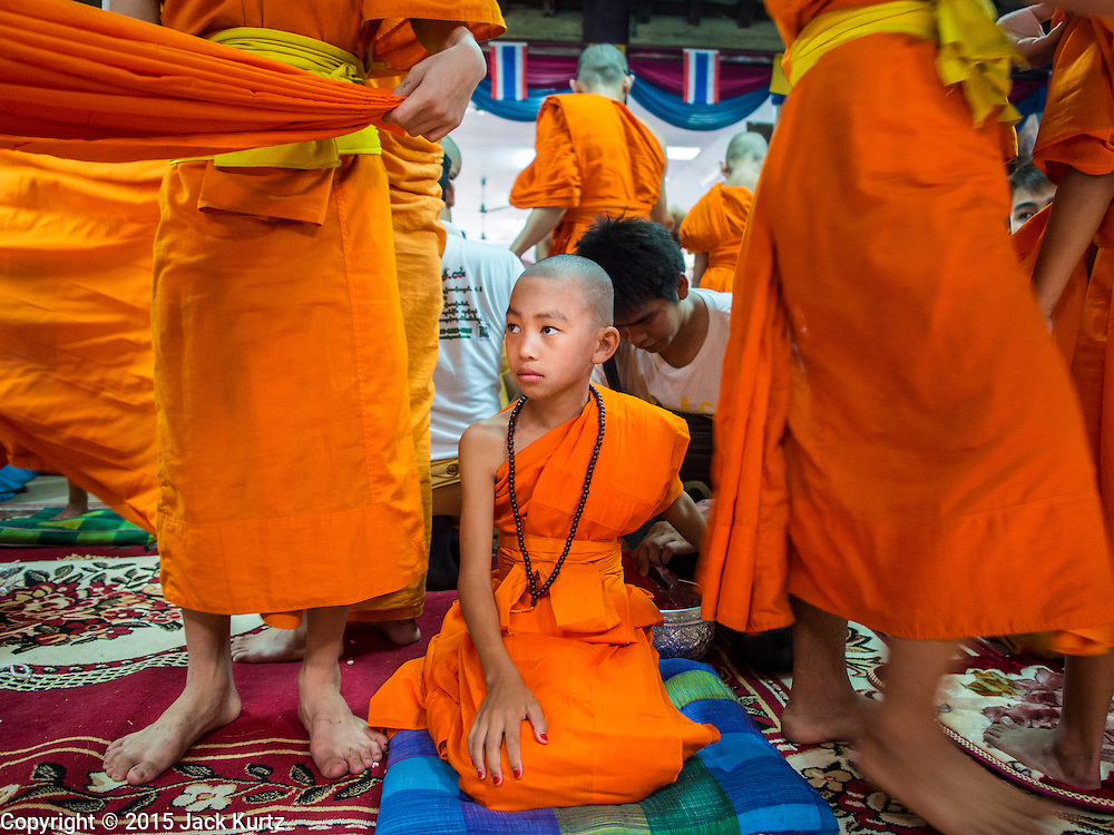 """06 APRIL 2015 - CHIANG MAI, CHIANG MAI, THAILAND: A boy in his monk's robes sits on the floor while other boys put their robes on during the ordination on the last day of the three day long Poi Song Long Festival in Chiang Mai. The Poi Sang Long Festival (also called Poy Sang Long) is an ordination ceremony for Tai (also and commonly called Shan, though they prefer Tai) boys in the Shan State of Myanmar (Burma) and in Shan communities in western Thailand. Most Tai boys go into the monastery as novice monks at some point between the ages of seven and fourteen. This year seven boys were ordained at the Poi Sang Long ceremony at Wat Pa Pao in Chiang Mai. Poy Song Long is Tai (Shan) for """"Festival of the Jewel (or Crystal) Sons.   PHOTO BY JACK KURTZ"""