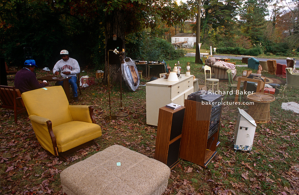 Two Georgian men play cards while waiting for passing trade during an outdoor yard sale in an Atlanta suburb.