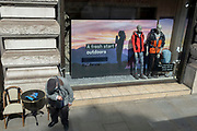 As Covid pandemic restrictions continue to ease, and non-essential retail businesses begin to re-open their shops, an elderly man sits down on a seat next to mannequins in the window of the Piccadilly branch of Outdoors supplier 'Cotswolds', 18th April 2021, in London, England.
