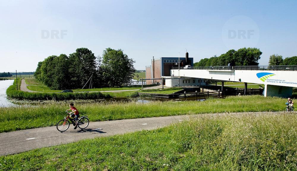 Nederland Moordrecht 24 mei 2007 20070524..Jongen fietst met op de achtergrond het gemaal de Abraham Kroes..Serie tbv Schieland en de Krimpenerwaard, deze zorgt als waterschap voor droge voeten en schoon water in een bepaald gebied. Het beheersgebied van Schieland en de Krimpenerwaard strekt zich uit tussen Rotterdam, Schoonhoven en Zoetermeer. Binnen dit gebied zorgt Schieland en de Krimpenerwaard voor de kwaliteit van het oppervlaktewater, het waterpeil en de waterkeringen. Daarnaast beheert Schieland en de Krimpenerwaard een aantal wegen in de Krimpenerwaard...Foto David Rozing