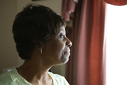 Portrait of an older woman looking out of a window,