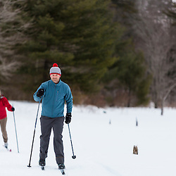 A man and woman cross country skiing on a frozen pond in Epping, New Hampshire.