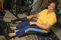 Older woman exercising on a rowing machine in her home gym,