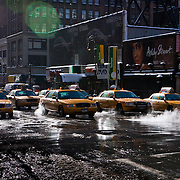 Line of yellow cabs warming up in the street.