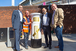 Local councillors Paul Swaddle, right, Gotz Mohindra and Robert Rigby with Tony Newlin for Royal Mail as he applies the vinyl decals ahead of Royal Mail unveiling a white-painted postbox outside Lords Cricket Ground with a plaque and graphics that celebrate England's ICC Cricket World Cup Victory. London, July 16 2019.