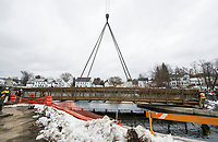 Crews work to lower a metal footbridge in place to connect the river walk behind Church Street on Thursday morning.  (Karen Bobotas/for the Laconia Daily Sun)