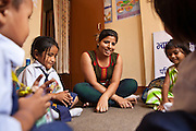 A children's activity facilitator, Sandi, is running a relationship building session with children in the Voice of Children centre in Kankeshori area of Kathmandu, Nepal.  The not-for-profit organisation supports street children and those who are at risk of sexual abuse through educational and vocational training opportunities, health services and psychosocial counseling.  These young children have recently been found by the charity and attend the children's drop-in centre where they play games and activities.