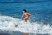 Young girl enjoys the ocean water, Cape Cod, Massachusetts, USA.