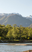 View of lake, trees and mountains, Sun behind trees,  Patagonia, Argentina, South America