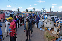 JOHANNESBURG, SOUTH AFRICA - APRIL 12: Homeless, unemployed and families below the bread line gather in Pageview, to meet Shareef and his team who handed out a total of 300 food parcels on April 12, 2020 in Johannesburg South Africa. Under pressure from a global pandemic. President Ramaphosa declared a 21 day national lockdown extended by another two weeks, mobilising goverment structures accross the nation to combat the rapidly spreading COVID-19 virus - the lockdown requires businesses to close and the public to stay at home during this period, unless part of approved essential services. (Photo by Dino Lloyd)