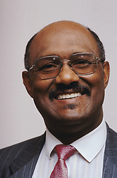 Portrait of man wearing suit and glasses smiling,