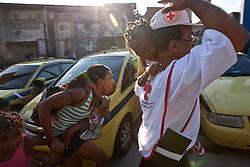 Médicos da cruz vermelha tentam ajudar moradores fora da favela do Morro do Alemão, em 27 novembro de 2010 no Rio de Janeiro, Brasil. Centenas de soldados e policiais se juntaram para uma repressão sobre as gangues de drogas. No início desta semana, a polícia forçou os membros das gangues saírem da favela Vila Cruzeiro, com o auxílio de tanques M113 transportadores blindados de pessoal. FOTO: Jefferson Bernardes/Preview.com