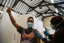 © Licensed to London News Pictures. 25/08/2021. London, UK. 19 year old Kezia De Oliveira gestures as<br /> Nassima Larbi, a NHS vaccinator, administers the Pfizer Covid-19 vaccine at a vaccination centre in Tottenham, north London. According to the Zoe Covid study, protection provided by two doses of the Pfizer and AstraZeneca Covid-19 vaccines starts to wane within six months. Photo credit: Dinendra Haria/LNP