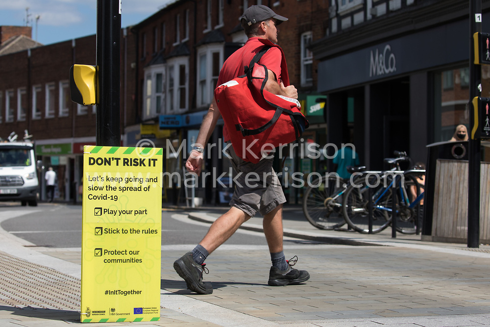 A man passes a Covid-19 public information display amid rising local concern regarding the spread of the Delta variant on 8th June 2021 in Wokingham, United Kingdom. Surge testing has been introduced in some local postcodes after a small number of cases of the Delta variant first identified in India were confirmed in the Wokingham area.