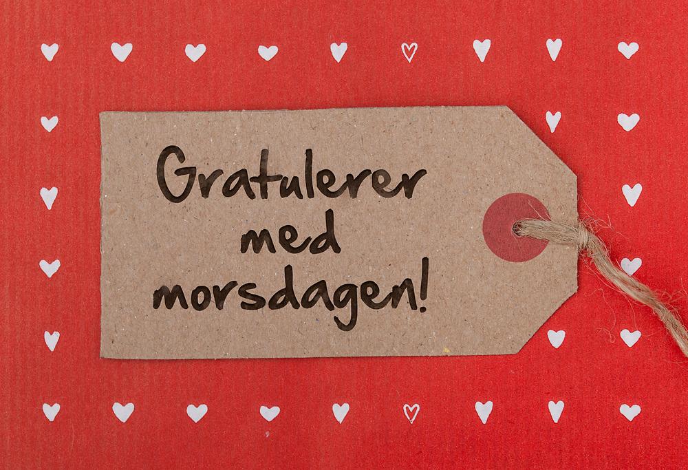 Gavelapp i grov papirstruktur med håndskrevet tekst «Gratulerer med morsdagen!». På rød papirbakgrunn med hvite hjerter.