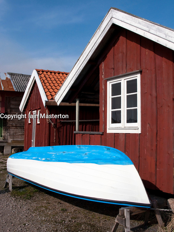 Wooden boat outside traditional red wooden hut in Grundsund village on Swedens Bohuslan coast