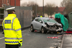 © Licensed to London News Pictures . 08/02/2013 . Salford , UK . Pictured a silver car understood to have been parked when the collision took place whilst behind under a green tarpaulin , the remains of a red Audi on its side with its door lying on the pavement as a policeman guards the scene . The scene on Leigh Road where a multi-vehicle pile up killed two , sparked a fire and damaged several cars and houses overnight , causing residents to be evacuated . Greater Manchester Police report seeing a stolen red Audi which they attempted to pursue prior to the crash . Photo credit : Joel Goodman/LNP