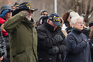 Goshen, New York - People in the crowd salute and hold their hands over their hearts during a Wreaths Across America ceremony at Orange County Veterans Memorial Cemetery on Dec. 16, 2017. About 3,000 wreaths were placed at graves, and small American flags were added to the wreaths at veterans' graves.