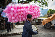 A teenage boy selling pink cotton candy outside a fairground on the 6th of March 2020 in Paudi, Sundarbazar, Lamjung District, Gandaki Pradesh, Nepal.  The fairground is part of the Holi celebrations, also known as Festival of Colours, is one of the most popular festivals in Nepal. It takes place on the full moon day in Nepali Fagu month (February to March in Solar Calendar) and lasts for 2 days.