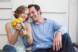 Happy woman receiving bunch of roses from man