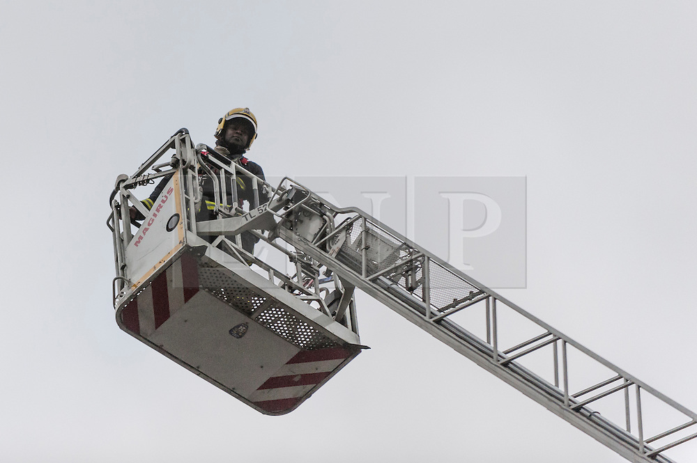 © Licensed to London News Pictures. 11/11/2015. London, UK. A fireman on a crane surveys the scene as a fire burns in a building on Fleet Street, to the left of the Goldman Sachs building.  A sign labelled Mary Queen of Scots house stands above the doorway.  Several fire engines, their crew and police are in attendance.  At present the cause is unknown. Photo credit : Stephen Chung/LNP