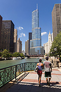 A couple walks along the Riverwalk on the Chicago River with the Trump Tower and skyline in Chicago, Illinois, USA
